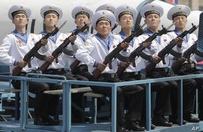 Navy personnel sit in front of a submarine-launched ballistic missile during a military parade on in Pyongyang, North Korea, to celebrate the 105th birth anniversary of Kim Il Sung, the country's late founder, April 15, 2017.