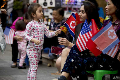 A girl plays with American, North Korean, and Vietnamese flags in a tourist area near Sword Lake in Hanoi, Vietnam,  Feb. 27, 2019.