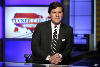 """FILE - Tucker Carlson, host of """"Tucker Carlson Tonight,"""" poses for photos in a Fox News Channel studio, in New York, March 2, 2017."""