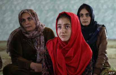 Women and young girls listen to Rasul (not pictured), an Iraqi Kurdish activist with the NGO WADI, as she speaks about the harm of genital mutilation in Sharboty Saghira, Iraq, Dec. 3, 2018.