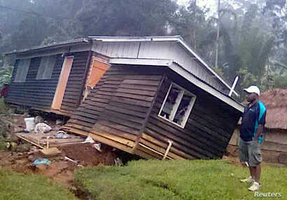 A local resident stands next to a damaged house near a landslide in the town of Tari after an earthquake struck Papua New Guinea's Southern Highlands, in this image taken Feb. 27, 2018, obtained from social media.