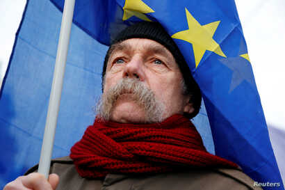 """A man holds an EU flag as he takes part in a protest against a proposed new labor law, billed as the """"slave law"""", in Budapest, Hungary, Jan. 19, 2019."""