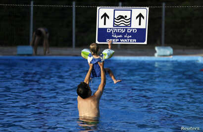 An Israeli man holds his son in the pool at Kibbutz Yad Mordechai, near the border with northern Gaza August 6, 2014. Israel withdrew ground forces from the Gaza Strip on Tuesday morning and started a 72-hour Egyptian-brokered ceasefire with Hamas as...