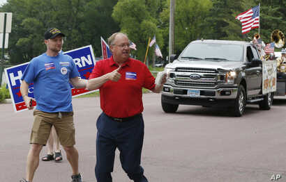 FILE - Minnesota congressional candidates, Democrat Dan Feehan (L) and Republican Jim Hagedorn, work a parade in Waterville, Minnesota, June 10, 2018.