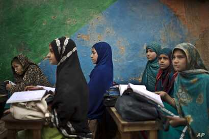 Afghan refugee schoolgirls attend a class at a makeshift school on the outskirts of Islamabad, Pakistan, Feb. 23, 2015.