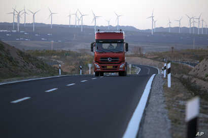 FILE - A truck travels down a highway with wind turbines in the background in northwestern China's Ningxia Hui autonomous region, Oct. 9, 2015.