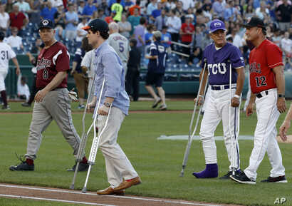 Injured aide Zach Barth (left) and Rep. Roger Williams, R-Texas, also on crutches walk off the field before the congressional baseball game, June 15, 2017, in Washington. The annual GOP-Democrats baseball game raises money for charity.