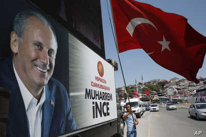 A supporter of Muharrem Ince, pictured left, the presidential candidate of Turkey's main opposition Republican People's Party, waves a Turkish flag prior to one of his rallies, in Istanbul, Turkey, June 16, 2018.