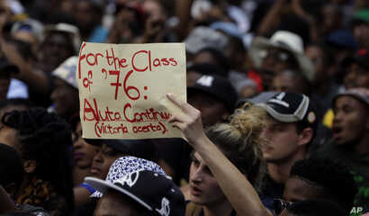 A student holds a placard during their protest against university tuition hikes outside the  ruling party African National Congress (ANC) headquarters in Johannesburg, South Africa, Thursday, Oct. 22, 2015.
