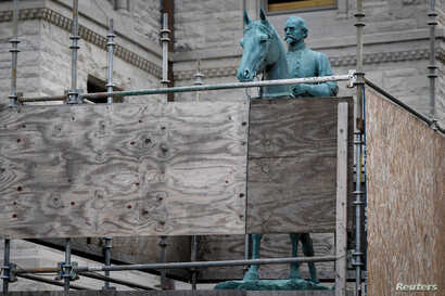 A monument to Confederate General John Hunt Morgan stands encased in a protective scaffolding because of local construction, outside the Old Courthouse in Lexington, Ky., Aug. 15, 2017.