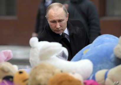 Russian President Vladimir Putin lays flowers at a memorial made for the victims of a fire in a multi-story shopping center in the Siberian city of Kemerovo, about 3,000 kilometers (1,900 miles) east of Moscow, Russia, Tuesday, March 27, 2018.