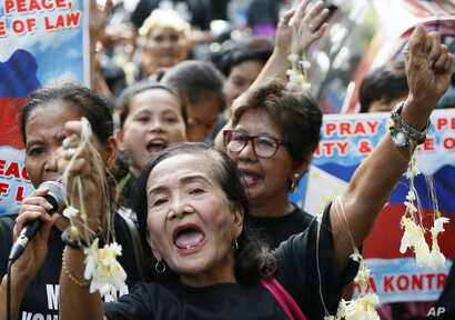 Filipinos and Vietnamese residents shout during a rally outside the Chinese Consulate in the financial district of Makati, east of Manila, Philippines, Aug. 6, 2016. They called on China to respect the international arbitration ruling favoring the Ph...