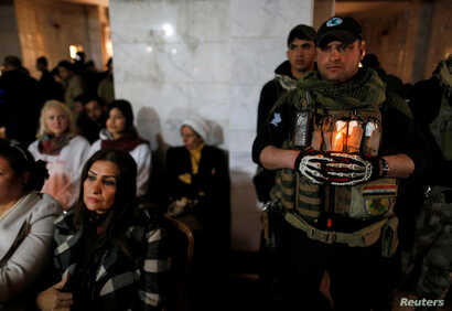 Iraqi Christians attend a Mass on Christmas Eve at the Mar Shimoni church in Bartella, Iraq, Dec. 24, 2016. Iraqi forces freed Bartella in October from IS control, but residents have not been able to return. They were bused in for the service.