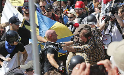 White nationalist demonstrators clash with counter demonstrators at the entrance to Lee Park in Charlottesville, Va., Aug. 12, 2017. Gov. Terry McAuliffe declared a state of emergency and police dressed in riot gear ordered people to disperse after c...