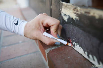 A homeowner uses a home lead test — which turns red when it detects the presence of lead — on the porch door of her old Spanish-style home, valued at more than $1.5 million, and dated from the 1920s, in San Marino, California, April 5, 2017.