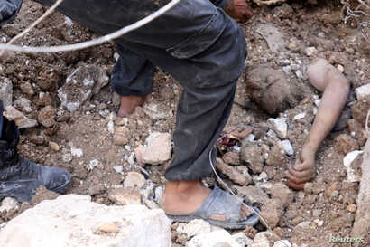 Men uncover a body from under debris after airstrikes in the rebel-held Karam Houmid neighborhood in Aleppo, Syria, Oct. 4, 2016.
