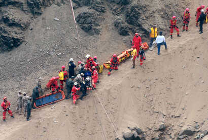 In this photo provided by the government news agency Andina, rescue workers surround an injured man on a stretcher who was lifted up from the site of a bus crash at the bottom of a cliff, after the bus was hit by a tractor-trailer rig in Pasamayo, Pe...
