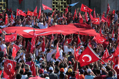 Turkish citizens wave their national flags as they protest against the military coup outside Turkey's parliament near the Turkish military headquarters in Ankara, Turkey, July 16, 2016.