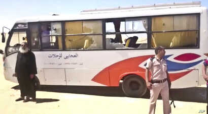 This image released by the Minya governorate media office shows a policeman and a priest next to a bus after militants stormed the bus in Minya, Egypt, May 26, 2017.