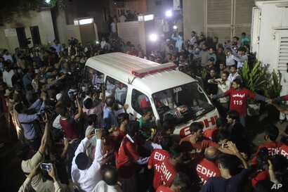 FILE - Volunteers of the Edhi Foundation escort the body of Pakistan's renowned social worker Abdul Sattar Edhi in an ambulance in Karachi, Pakistan, July 8, 2016.
