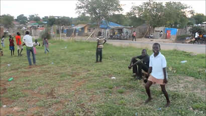 A young South Sudanese boy celebrates after scoring a goal on a ramshackle football pitch near Juba.