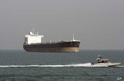 FILE - An Iranian Revolutionary Guard speedboat passes near an oil tanker, July 2, 2012. A collision late Saturday off the eastern coast of China left 30 Iranians missing.