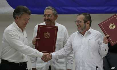 Colombian President Juan Manuel Santos, left, and Timoleon Jimenez, commander of the Revolutionary Armed Forces of Colombia, or FARC, shake hands during a signing ceremony of a cease-fire and rebel disarmament deal, in Havana, Cuba, June 23, 2016.