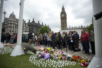 Staff from Britain's opposition Labour Party stand together before placing floral tributes for their colleague Jo Cox, the 41-year-old British Member of Parliament shot to death yesterday in northern England, on Parliament Square outside the House of...
