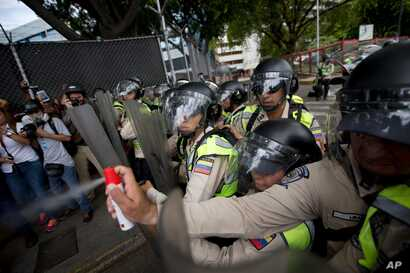 A Bolivarian National Police officer aims pepper spray at opposition leader Henrique Capriles during a protest in Caracas, Venezuela, June 7, 2016.
