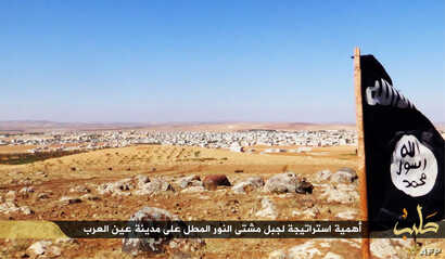 FILE - An image made available by propaganda Islamist media outlet Welayat Halab allegedly shows the trademark Jihadist flag positioned in the Mishtenur area, a plateau south of Kobani, Syria.