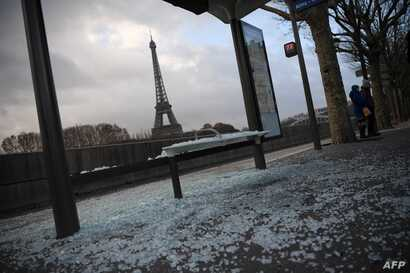 """A picture taken in Paris, Dec. 9, 2018, shows a broken bus stop and (background) the Eiffel tower a day after a """"yellow vest"""" protests as part of a fourth weekend of nationwide protests."""