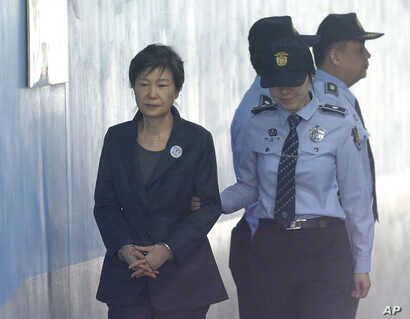 FILE - In this Oct. 10, 2017 file photo, Former South Korean President Park Geun-hye, left, arrives to attend a hearing on the extension of her detention at the Seoul Central District Court in Seoul, South Korea.