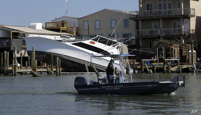 An emergency response boat passes a boat that was displaced by the effects of Hurricane Harvey,  in Port Aransas, Texas, Aug. 30, 2017.