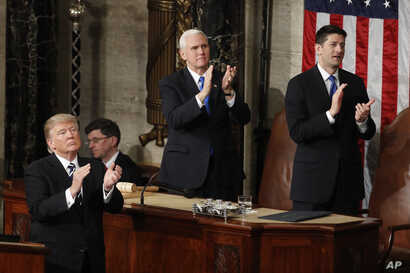 """President Donald Trump, Vice President Mike Pence and House Speaker Paul Ryan applaud Carryn Owens, widow of Navy SEAL William """"Ryan"""" Owens, on Capitol Hill in Washington, Feb. 28, 2017, during the president's address before a joint session of Co..."""