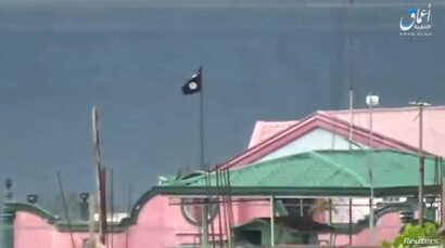 A still image taken from a video posted to a social media website by the Islamic State-affiliated Amaq News Agency on June 12, 2017, shows a black flag perched on a building in Marawi City, Philippines.