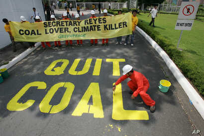 """FILE - Activists from the environmentalist group Greenpeace paint the words """"Quit Coal"""" on the driveway of the Department of Energy at Manila's Taguig city Tuesday June 3, 2008 in another protest urging the Philippine Government to stop building and ..."""