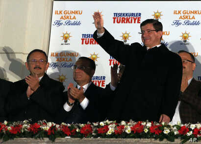 Turkish Prime Minister Ahmet Davutoglu salutes supporters gathered outside the ruling Justice and Development Party headquarters in Ankara, Turkey, Sunday, Nov. 1, 2015.