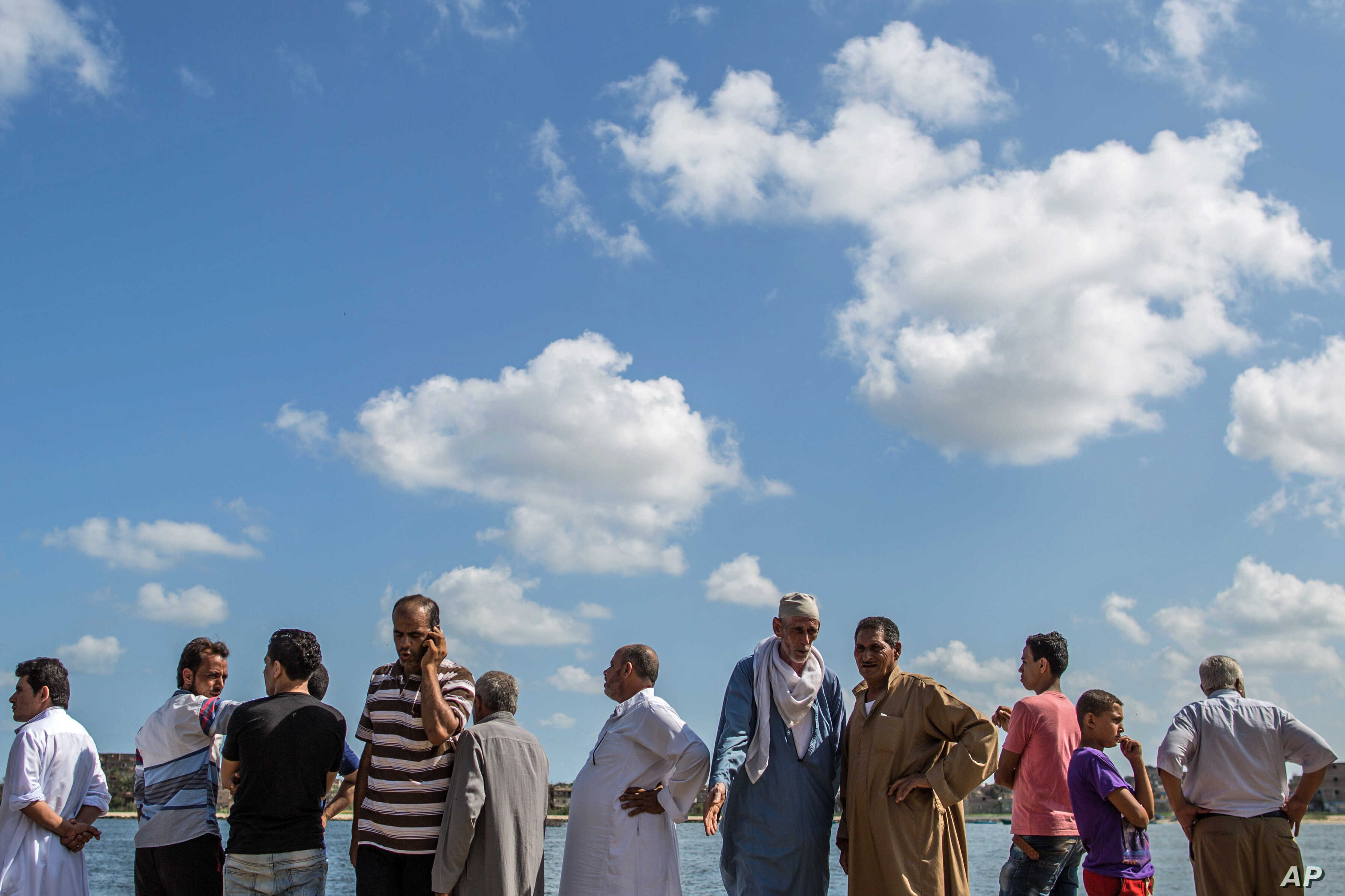Relatives of Egyptians whose Europe-bound boat capsized off Egypt's Mediterranean coast watch departing boats that are participating in a search operation, in Rosetta, Egypt, Sept. 22, 2016.