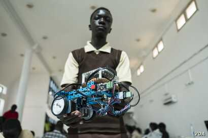 Mohamed Sidy, 14 years old and from Dakar, holds up his team's robot at the 2017 Pan-African Robotics Competition in Dakar, Senegal, May 19, 2017. (R. Shryock/VOA)