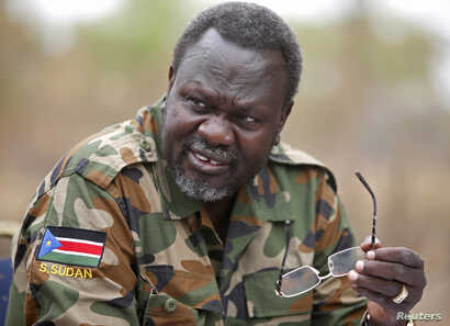 South Sudan's rebel leader Riek Machar speaks to rebel General Peter Gatdet Yaka (not seen) in a rebel controlled territory in Jonglei State, Feb. 1, 2014.