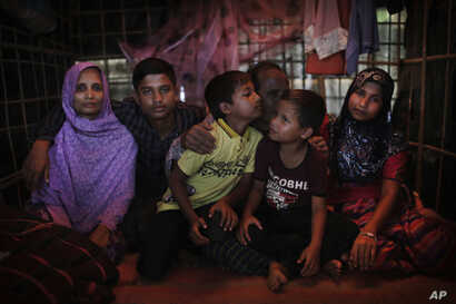 In this Nov. 25, 2017, photo, Bodru Duza, 52, third from right, kisses his sons as he sits for a portrait with members of his family in a tent in Kutupalong refugee camp in Bangladesh.