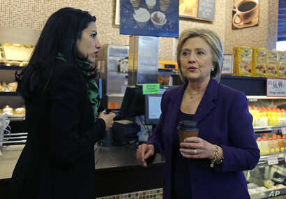 FILE - Democratic presidential candidate Hillary Clinton, right, chats with her aide, Huma Abedin during a campaign stop at Market Basket Supermarket, Feb. 2, 2016, in Manchester, N.H.