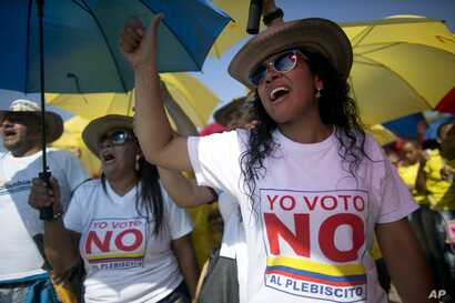 """Demonstrators yell """"No to the plebiscite"""" to protest the government's peace agreement with the Revolutionary Armed Forces of Colombia (FARC), to be signed later in the day in Cartagena, Colombia, Sept. 26, 2016."""