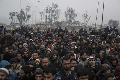 Displaced Iraqi men, fleeing fighting between Iraqi security forces and Islamic State militants, wait for a security check before being transferred to a camp on the western side of Mosul, Iraq, March 23, 2017.