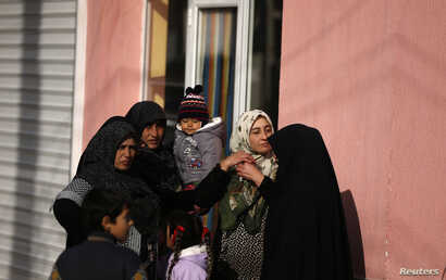 FILE - Women gather near a house during a specialized operation in a Roma neighborhood in the city of Pazadzhik, Bulgaria, Nov. 25, 2014.