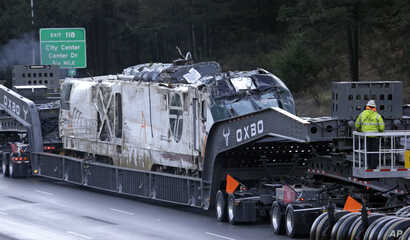 The engine from an Amtrak train that crashed onto Interstate 5 two days earlier is transported away from the scene, Dec. 20, 2017, in DuPont, Washington.