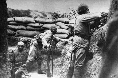 FILE - In this 1915 file photo, a Turkish soldier takes aim at British troops, while another watches carefully, from a trench in Gallipoli, Turkey.