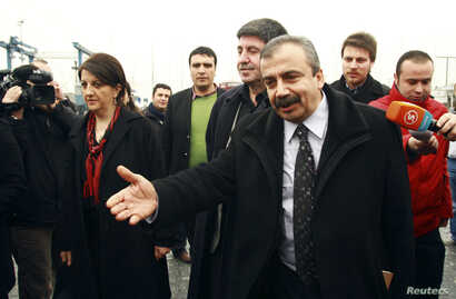 FILE - Pro-Kurdish politicians Sirri Sureyya Onder (R), Pelvin Buldan (L) and Altan Tan (C), are surrounded by media members before leaving for Imrali island in Istanbul, Feb. 23, 2013.