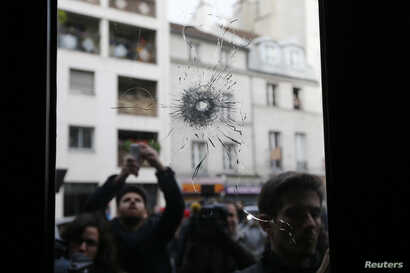 Journalists work outside a restaurant where bullet impacts are seen the day after a series of deadly attacks in Paris, France, Nov. 14, 2015.
