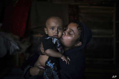 In this Nov. 27, 2017, photo, Asmida kisses her 9 month-old son, Mohamed Umair, in a refugee camp in Bangladesh. Asmida lost track of the baby when she tried to stop soldiers from dragging her husband away after they massacred her village in Myanmar'...